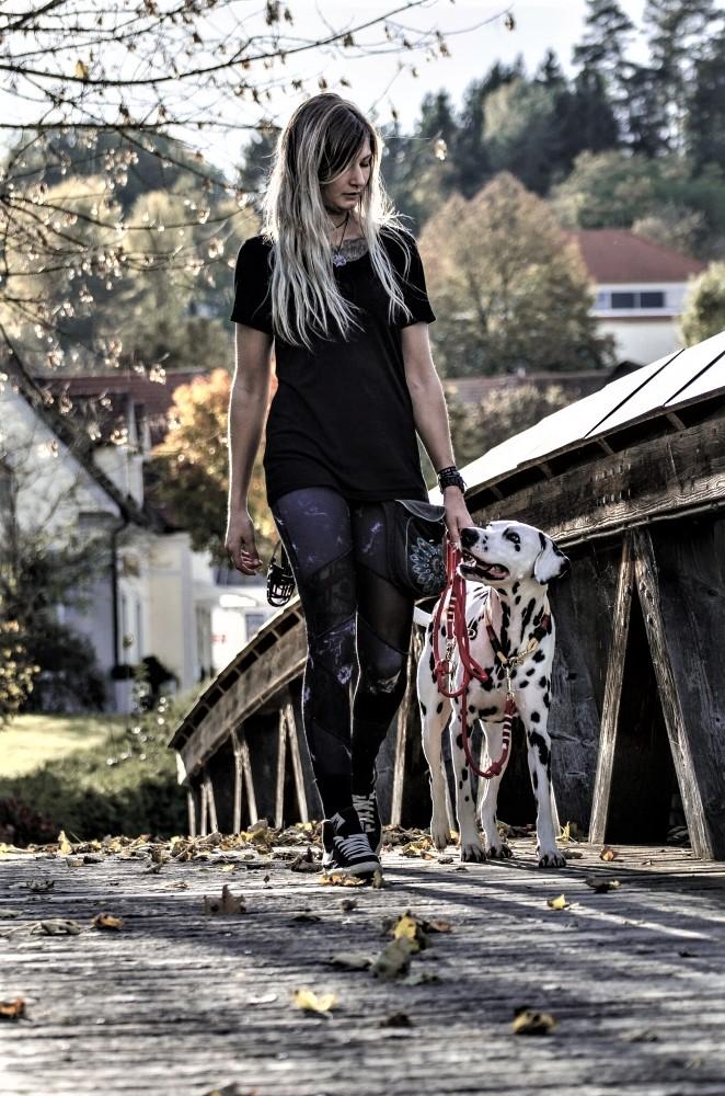 Junge Frau führt Dalmatine an lockerer Leine über eine Brücke